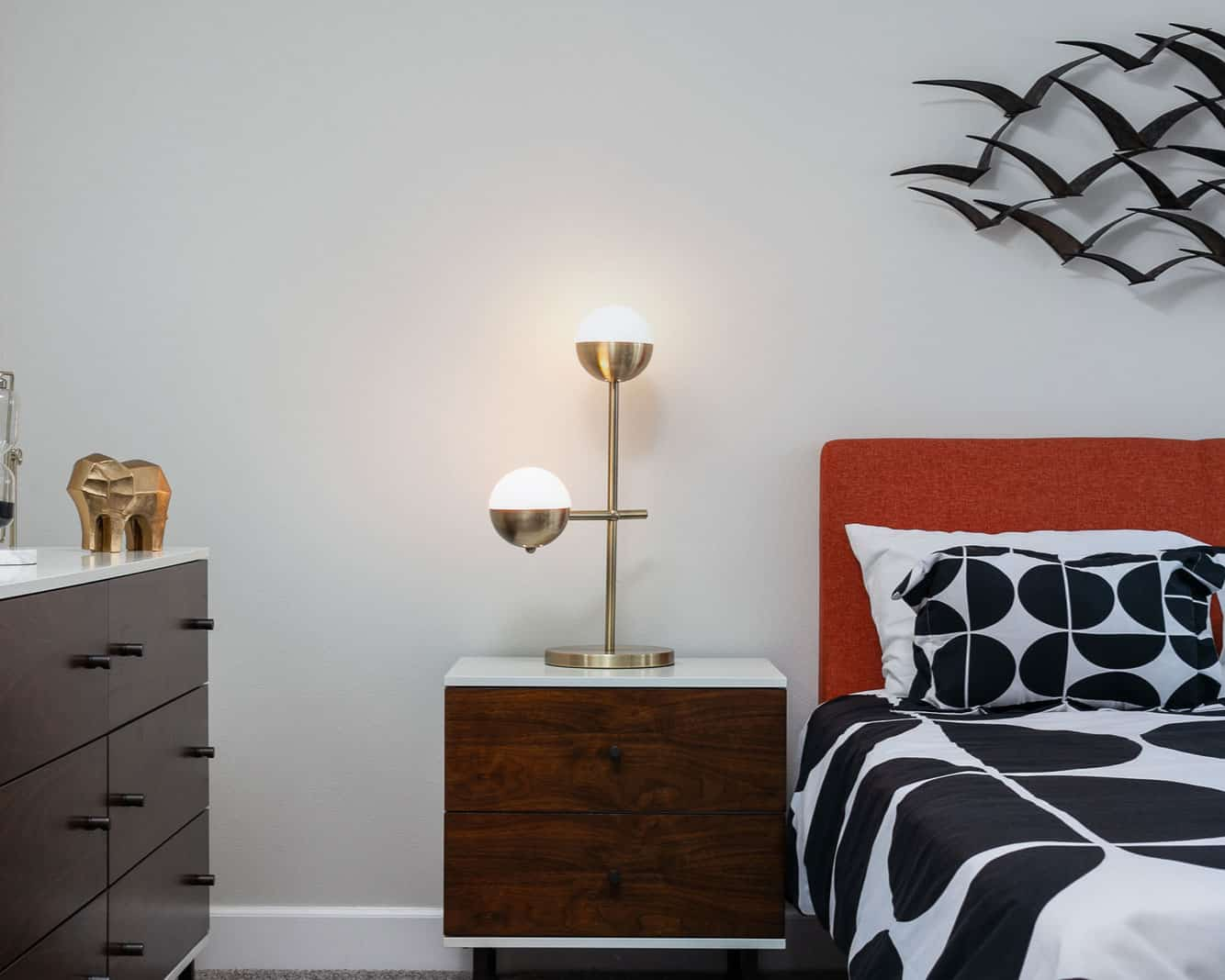 side table with lamp in between cabinet with gold elephant on top and a bed with orange head board, black and white bedding
